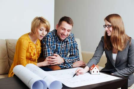 Junge Paare, die Layouts eines zukünftigen Hauses mit einem Architekten zu diskutieren photo