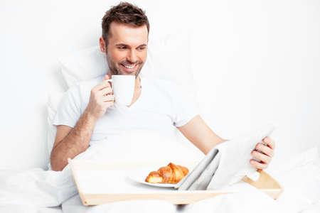 hombre comiendo: Apuesto joven leyendo un periódico de la mañana en la cama Foto de archivo