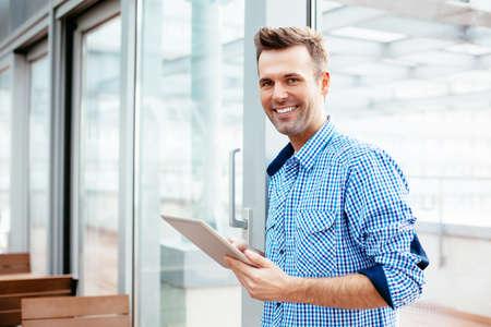 Glückliche junge Mann lächelnd in die Kamera mit einer Tablette in der Hand