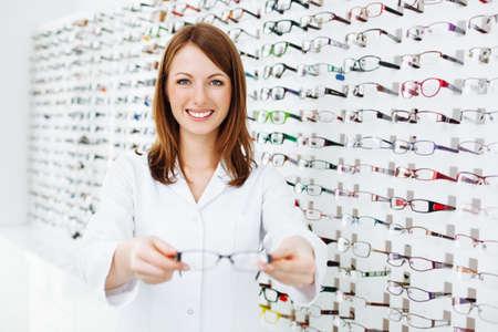 Optician presenting  eyewear frames Standard-Bild