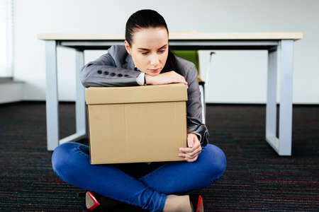 let go: Photo of a depressed woman sitting on the floor after being let go from work