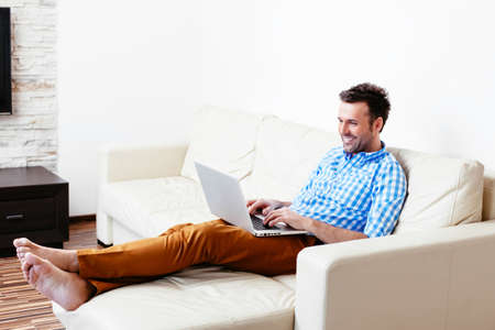 Smiling young man relaxing on a sofa with his laptop