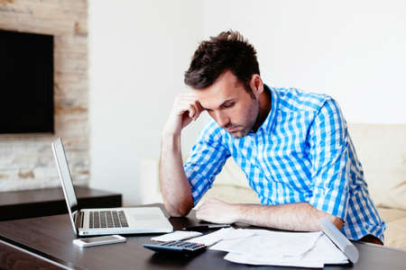 sadness: Young sad looking man exemining his household expenses Stock Photo