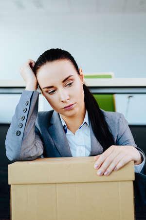Porträt einer Frau mit einem Karton auf dem Schoß, die entlassen wurde,