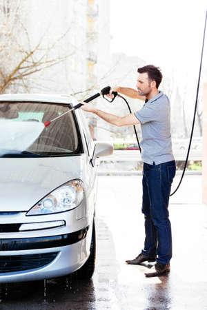 Junger Mann mit seinem Auto sauber Spritzen