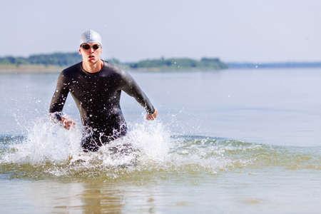 Schwimmer Triathlon drinn, während aus dem Wasser laufen