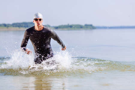 water sports: Triathlon swimmer splashing around while running out of water
