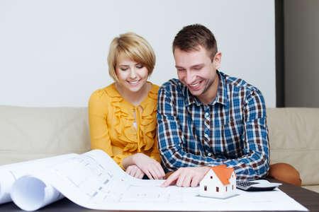 Junge glückliche Paare, die auf einem Sofa sitzt und an einem Plan suchen photo