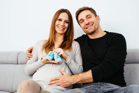 Pregnant young couple posing on the couch
