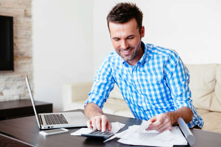 Lachende jonge man het analyseren van zijn uitgaven en online betalen