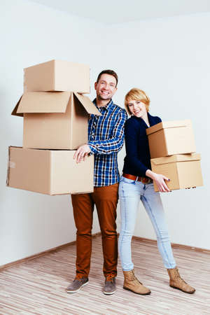 Young couple holding carton boxes and moving in