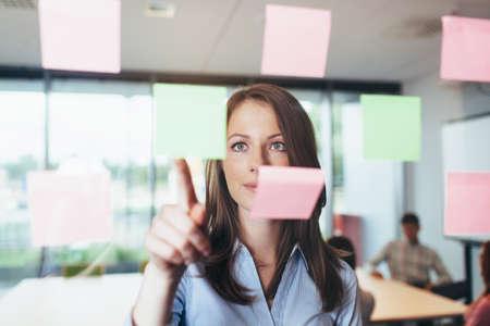 Portrait eines weiblichen Berufs bei einigen Haftnotizen suchen im Büro zu einer Glaswand geklebt photo