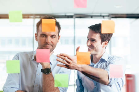 couching: Two students agreeing on a idea written on a sticky note