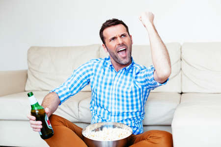 Aufgeregter Fan beobachtet den Sieg seines Teams im Fernsehen
