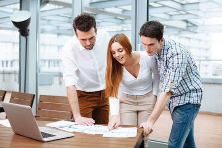 Junge Geschäftsleute diskutieren Finanzdaten im Büro photo