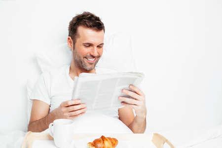 bedlinen: Portrait of a handsome man reading a newspaper in bed