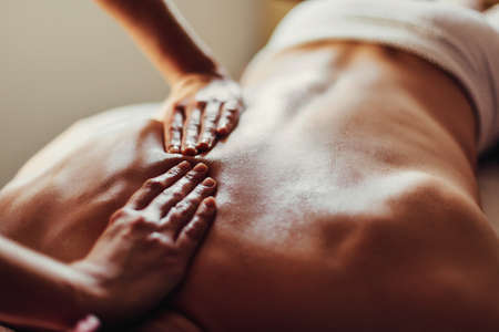 Close-up of masseurs hands and a clients back