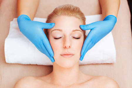 Portrait of a young woman getting a face massage