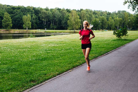 woman running: Photo of a young woman jogging in the park