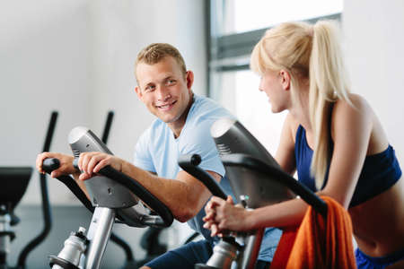Couple training indoor cycling in a gym