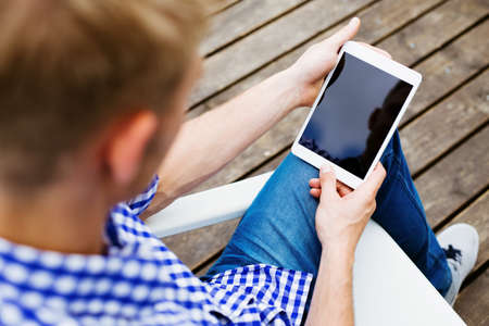 Closeup of man sitting with digital tablet