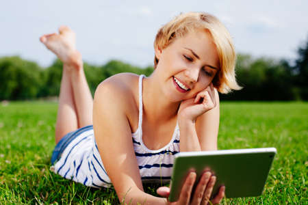 green technology: Photo of a young woman relaxing on the grass with a tablet in her hands Stock Photo