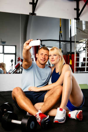 atractive: Photo of a young sporty couple taking a selfie in a fitness club