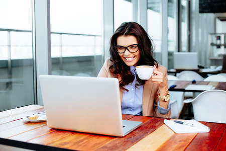 Pretty lady holding a cup of coffee and using a laptop Stock Photo