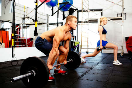 Young couple training with weights at gym
