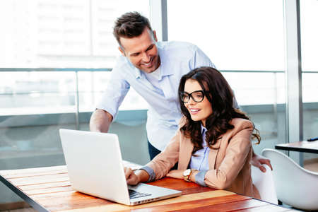 businessman in office: Young couple pointing to a laptop display. Business concept