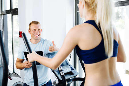 atractive: Young woman exercising on an orbitrec with an assissting trainer Stock Photo