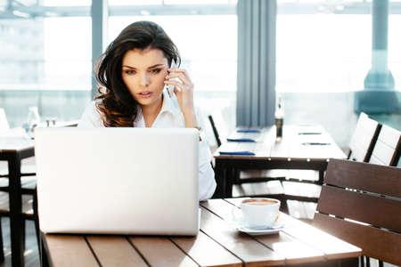 Junge hübsche Frau am Telefon zu sprechen und an ihrem Laptop in einer Kantine suchen Lizenzfreie Bilder