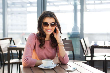 Young smiling woman sitting at a table with a cup of coffee and waiting