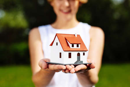 Foto van een jonge vrouw die een miniatuurhuis houdt Stockfoto