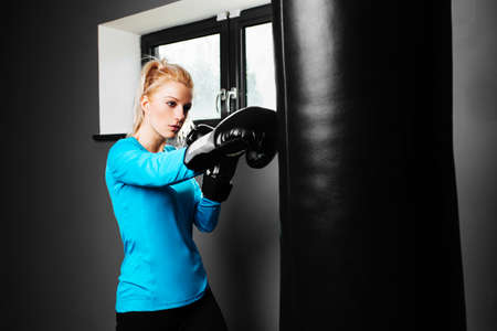 punched out: Young female athlete in a boxing training