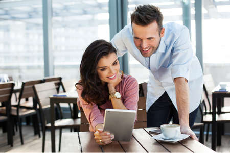 Couple of young smiling people looking at a digital tablet Stock Photo
