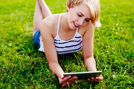 Photo of a woman relaxing on the grass with a tablet in her hands