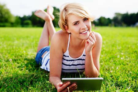 Portrait einer hübschen Frau auf dem Rasen mit einem digitalen Tablette in der Hand liegend Lizenzfreie Bilder