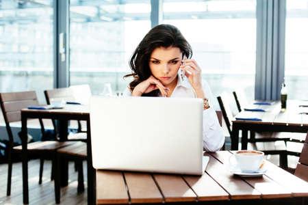 Attraktive junge Frau am Telefon zu sprechen und eine Website zu überprüfen