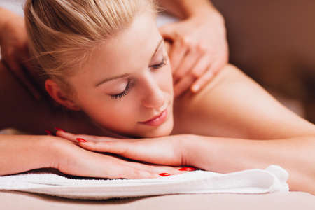causcasian: Attractive young beauty relaxing during  a back massage Stock Photo