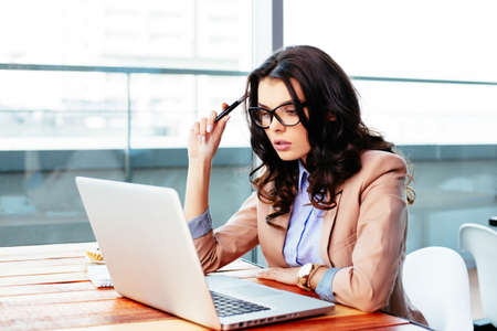 portables: Young woman deep in thought in front of a laptop Stock Photo