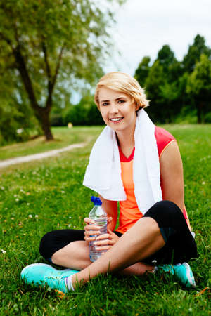 Smiling woman runner relaxing on the grass after a run