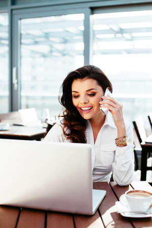 Attraktive Geschäftsfrau arbeitet an ihrem Laptop und spricht am Telefon
