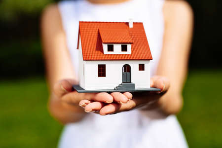 miniature: Photo of a woman holding a miniature house Stock Photo