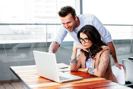 Junge freie Mitarbeiter mit einem Laptop und am Dispaly suchen. Geschäftskonzept Lizenzfreie Bilder
