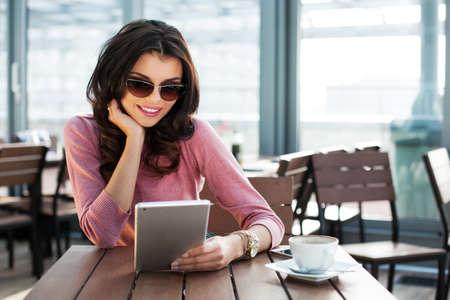 Junge attraktive Frau, die auf ihrem Tablet-Surfen während sitzen in einem Café Lizenzfreie Bilder