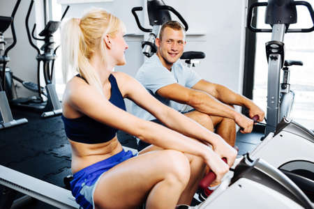 Junge Frau mit einem persönlichen Trainer auf einer Reihe Maschine ausüben
