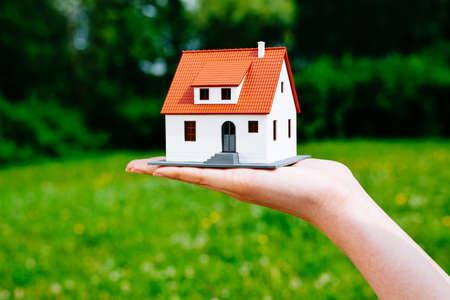 新しいホーム コンセプト - 小さな家の置物を持っている女性の手のクローズ アップ