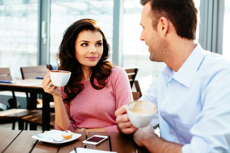 brak: Young couple having a conversation over a cup of coffee