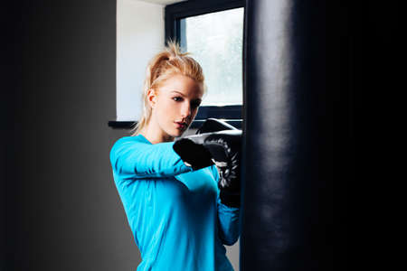 punched out: Blonde woman perfecting her boxing skills Stock Photo